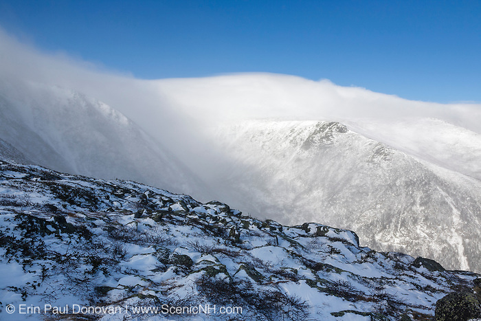Mount Washington - Tuckerman Ravine in extreme weather conditions from Boott Spur Trail in the White Mountains, New Hampshire USA during the winter months. Strong winds cause snow to blow across the mountain tops.