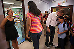 Yokayra Fernandez-Haghighi, center, talks with 2nd Grade Special Ed teacher Melissa Berkowitz, left, while her husband Saeid Haghighi kisses his son Jesus Haghighi, 7, good-bye, watched by their daughter Victoria Haghighi, 12, center, at PS85 in Fordham Heights in The Bronx, NY on September 11, 2013.