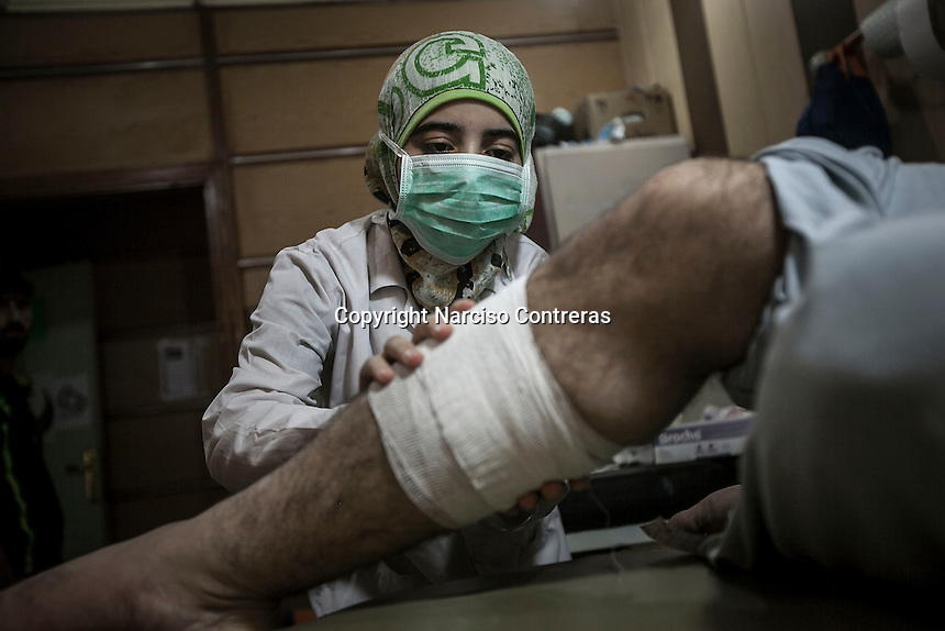 Jasmin, a 17 years old nurse, bandages an injured man (non portrayed) as she works full time at hospital in an undisclosed location inside one rebel controlled area of the northern Syrian city of Aleppo.