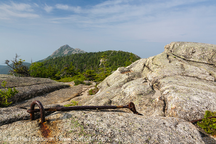 Mount Chocorua from Middle Sister Trail in the White Mountains, New Hampshire on an early hot and hazy summer day. Pieces of the old fire tower along Middle Sister Trail can be seen in the foreground. This fire tower was in operation from 1927-1948.