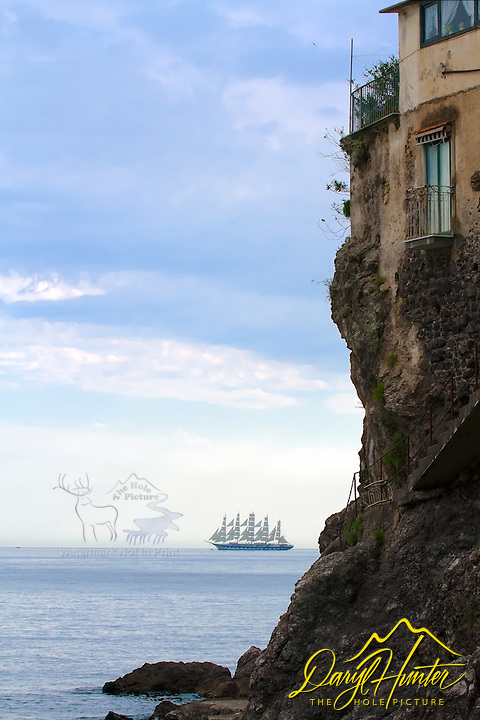 A tall ship sails past along the Amalfi Coast. The villages of Postiano, Amalfi, Manori and others of the Amalfi coast seem to be lost in a time warp of antiquity.  Whitewashed and pastel colored villas cling precariously to unforgiving slopes while sea and sky merge in one vast blue horizon.