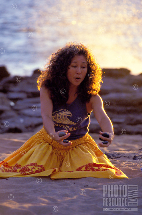 Hula dancer at Makapuu point dancing a noho hula with ili ili stones at sunrise on the beach