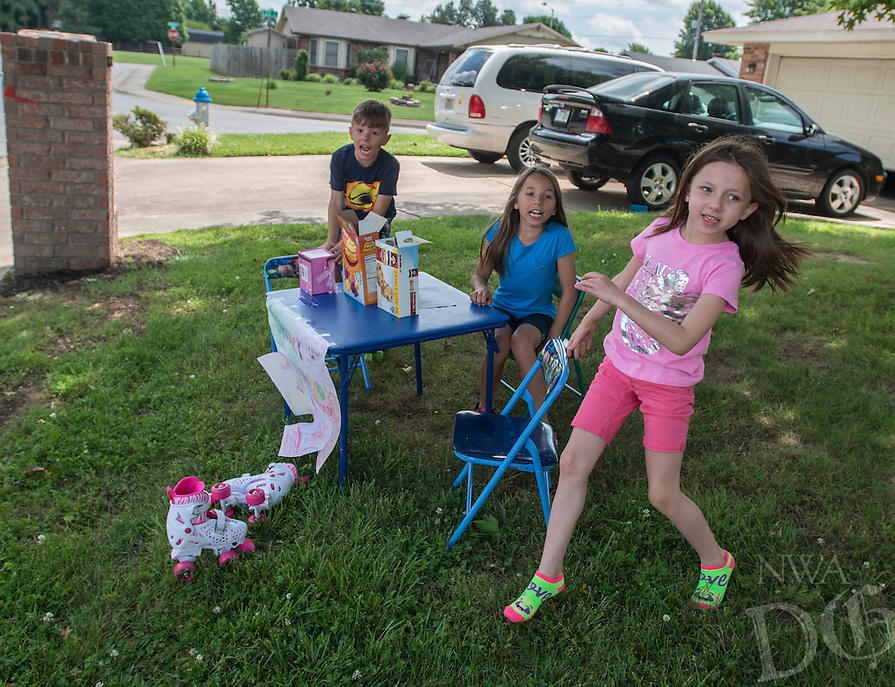 NWA Democrat-Gazette/ANTHONY REYES &bull; @NWATONYR<br /> Raiden Dale, 7, (from left), Kaylen Dale, 7, and Emily Dale, 9, call out to passerbys Monday June 13, 2016 as they sell snacks foods outside their home in Springdale. The trio were selling granola bars, gummy fruit snacks and puppets to passing motorists on their neighborhood street. Raiden hopes to buy trading cards with his share of the money.