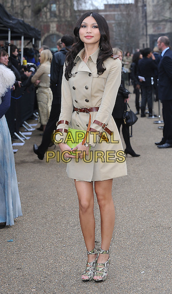GEMMA CHAN.The Burberry Prorsum Fashion Show during London Fashion Week Autumn/Winter 2011, Kensington Gardens, London, England..21st February 2011 .LFW full length brown belt buckles green clutch bag mac beige snakeskin sandals .CAP/BEL.©Tom Belcher/Capital Pictures.