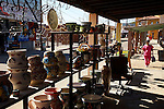Local pottery for sale on sidewalk next to female dental hygienist in uniform, Los Algodones, B.C, Mexico.