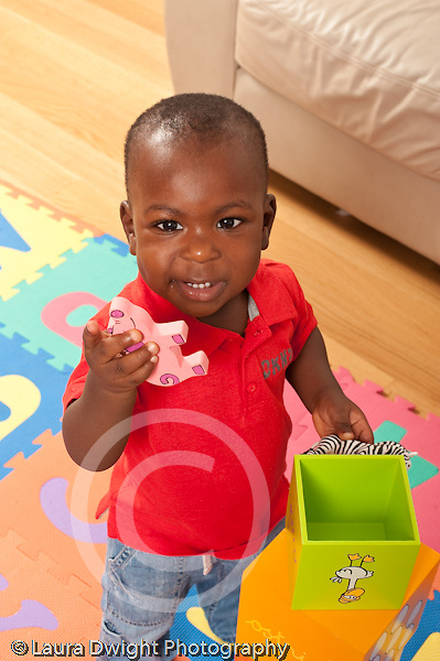 12 month old baby boy standing playing with toys looking at camera saying word holding toy animal pig vertical