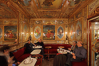 The Sala del Senato or Senate Hall in the Caffe Florian, with paintings by Giacomo Casa, including the Age of Enlightenment (centre), 19th century, on St Mark's Square or Piazza San Marco, Venice, Italy. This coffee house was founded in 1720 and is one of the oldest continuously operated cafes in the world. It was restored in 1858 by Lodovico Cadorinj and artists employed to paint on the walls. The city of Venice is an archipelago of 117 small islands separated by canals and linked by bridges, in the Venetian Lagoon. The historical centre of Venice is listed as a UNESCO World Heritage Site. Picture by Manuel Cohen