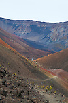 A hiker on the trail through an area known as Pele's Paintpot due to the colorful lava rock in Haleakala National Park on the island of Maui, Hawaii, USA