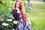 Female 20-25 years of age with long red hair wearing flowery summer dress standing with eyes closed