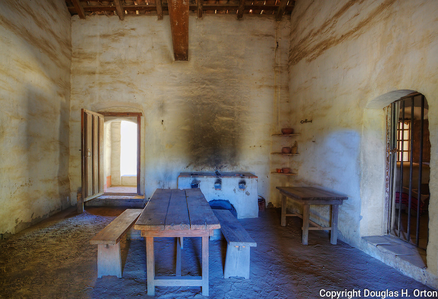 Kitchen with wood fired adobe stove and rough hewn table, dirt floor and adobe walls with officer's apartment in background at Mission La Purisima State Historic Park, Lompoc, California.  Mission La Purisima, founded in 1787 by Franciscan Padre Presidente Fermin Francisco Lasuen. La Purisima was the eleventh mission of the twenty-one Spanish Missions established in what later became the state of California.
