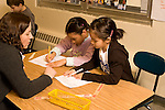 Education elementary Grade 3 science classroom female teacher explaining experiment method to two female students  horizontal
