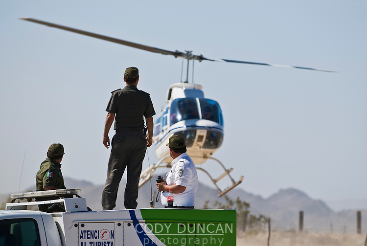 Green Angels, assistants to tourists in Mexico, watching chase helicopter landing at finish of 2008 San Felipe Baja 250, Mexico