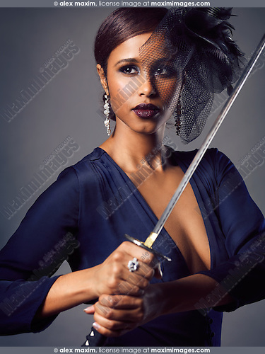 Portrait of a beautiful woman with black veil holding a Katana sword in her hands