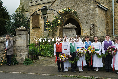 Charlton-on-Otmoor Oxfordshire 1st of May Day Celebrations. Children from the Church of England St Mary the Virgin Primary School process to the village church to have their May garlands blessed. They sing the traditional May Day song twice on route and once outside of the church.2014.