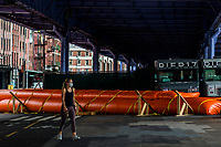 "NEW YORK, NY - AUGUST 4: woman walks next to water barriers used to prevent flooding at the South Street Seaport as city gets ready for tropical storm Isaias on August 4, 2020 in New York City. The Tri-State area ""New York, New Jersey and Connecticut"" is preparing for torrential rain, strong winds from Tropical storm Isaias. (Photo by Eduardo MunozAlvarez/VIEWpress)"
