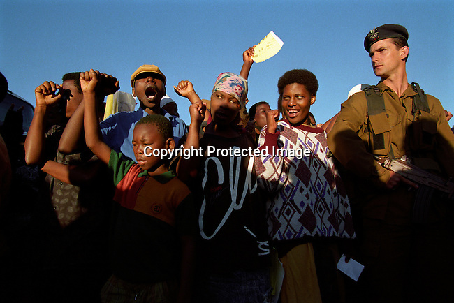 South Africans sing while queuing to vote in the historic first democratic election on April 27, 1994 in Lindelani, in Natal Province, South Africa.  President Nelson Mandela voted here 6AM and his car passed by as these youngsters sang to honor him. President Nelson Mandela served one five-year term and retired in 1999, and the current President, Thabo Mbeki became the leader.