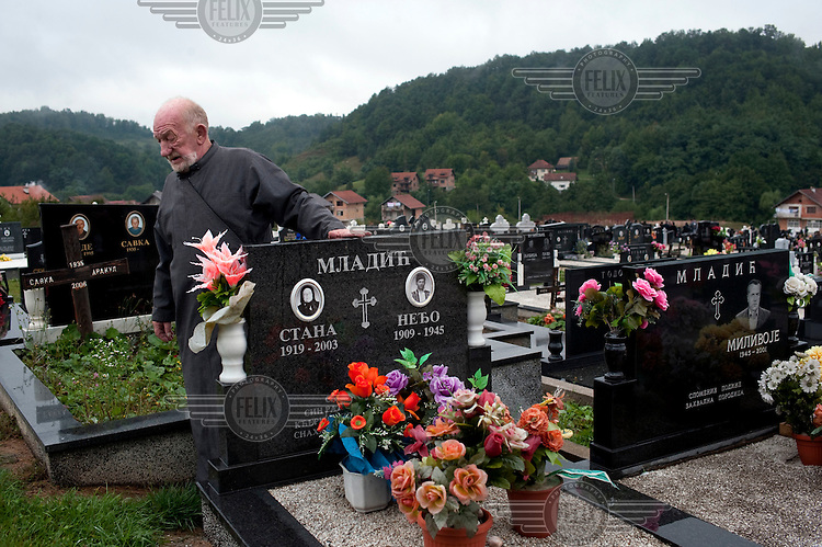Vojislav Carkic, a priest and Major in the army of Republika Srpska, stands over the graves of Ratko Mladic's mother, father and brother in the village of Donje Miljevici. Former Bosnian Serb general Ratko Mladic is one of the most sought after suspects from the Bosnian conflict. He has been indicted by the UN war crimes tribunal on charges of genocide and crimes against humanity The hill behind Carkic overlooks the city of Sarajevo and marks the Serbian front line during the siege of the city.