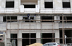 Palestinian laborers construction work at building still under construction, in Gaza city on October 28, 2017. Property owners in the Gaza Strip suffer from weak market and sales, and according to World Bank's report Gaza's economy is not expected to return to pre-war level at least until 2018. Photo by Mohammed Asad