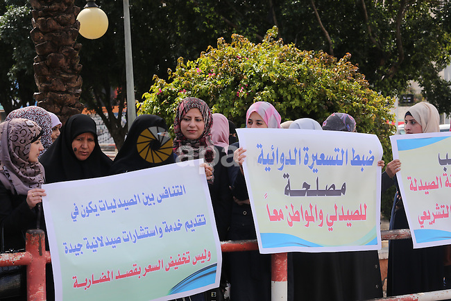 Palestinian pharmacists hold banners during a protest against the pricing treatment in front of the Legislative Council, in Gaza city, on March 16, 2016. Photo by Mohammed Asad