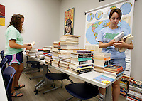 NWA Democrat-Gazette/DAVID GOTTSCHALK Delaney Dunahoo (cq) (left) and Allison Thomey, both sophomores, sort books in the new classroom of Tad Sours Tuesday, August 4, 2015 at Starr Scholar Center the new location of the Fayetteville campus of Hass Hall. Classes begin Thursday at the new location, that has 20 classrooms and office spaces, on Front Street just south of Joyce Boulevard.