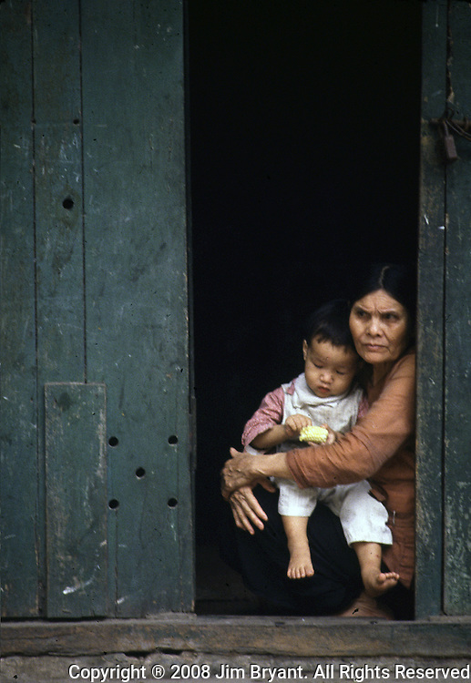 An  old woman and her granddaughter, eating an ear of corn, sit in the doorway of their home in Hanoi, North Vietnam.  Many families live poorly in gloomy ghettos - old French villas fallen to shabby decay. (Jim Bryant Photo).....