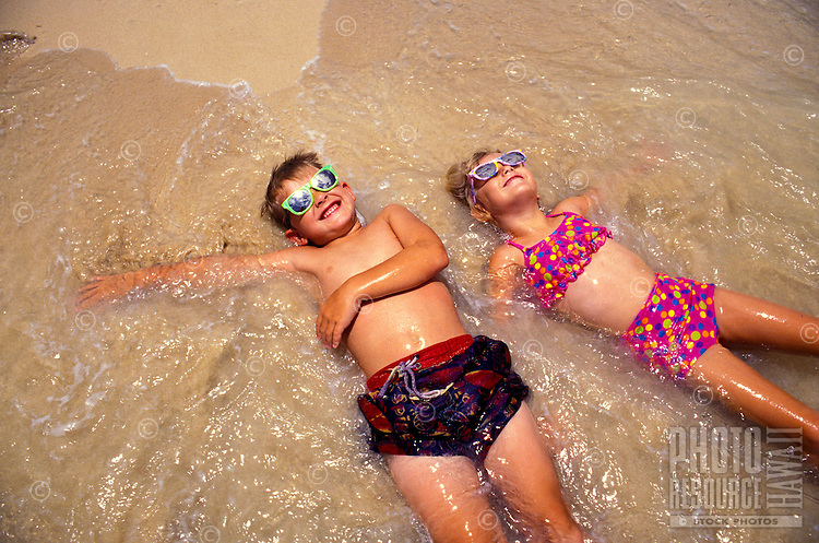 Young siblings  ( ages 6 & 7 ) frolic in the sand and surf of Hawaii's pristine beaches.