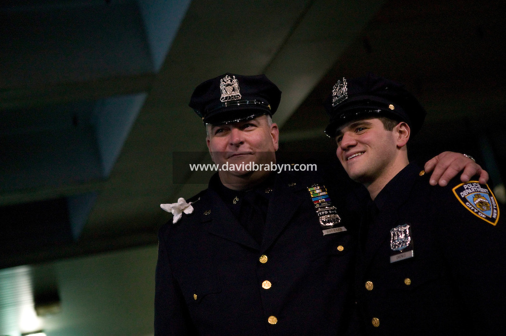 Newly sworn in Police Officer Joseph Uvenio (R) poses with his step-father Police Officer Glen Bressan, who is retiring this year after 26 years on the force, for his family after graduating with the NYPD Class of 2005, December 29, 2005, in New York City. 1,735 new police officers were sworn in during the ceremony.