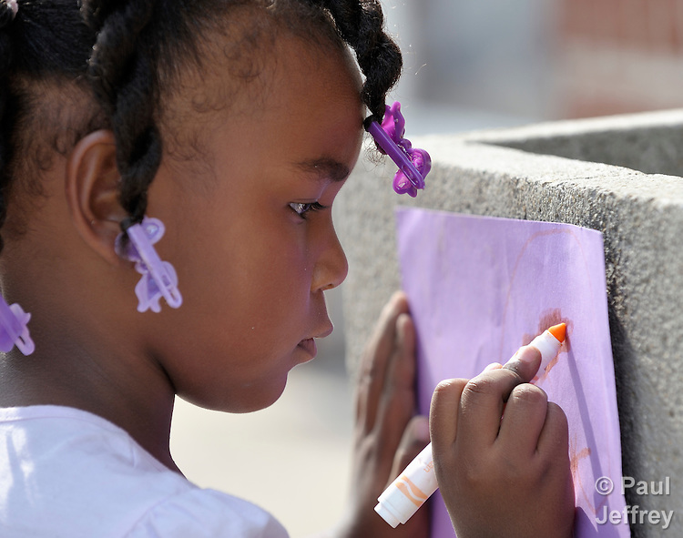 A girl draws a picture in a day care center run by the Lessie Bates Neighborhood House in East St. Louis, Illinois.