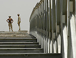 Royal Engineers stand at the end of a partially dismantled bridge in the Rumaylah Oilfields. The bridge was built during the 2003 invasion of Iraq to replace a bombed out span.