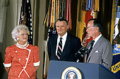 United States President George H.W. Bush and first lady Barbara Bush present the Presidential Citizens Medal to Deputy Director of Central Intelligence Richard Kerr during a ceremony in the East Room of the White House in Washington, DC on July 3, 1991. Kerr is being honored for his efforts to ensure the success of Operation Desert Shield / Operation Desert Storm and the liberation of Kuwait.<br /> Credit: Ron Sachs / CNP