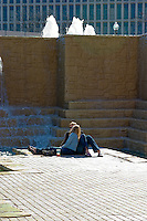 A young couple sitting in front of waterfalls at Hemisfair Park in San Antonio, Texas, USA.