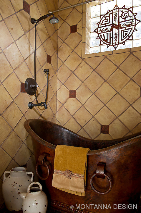 Southwest inspired bath with a hammered copper tub and custom tile