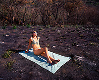 Bikini swimsuit girl sunbathing in burned-out field, Kaena Point, Oahu, Hawaii, USA.