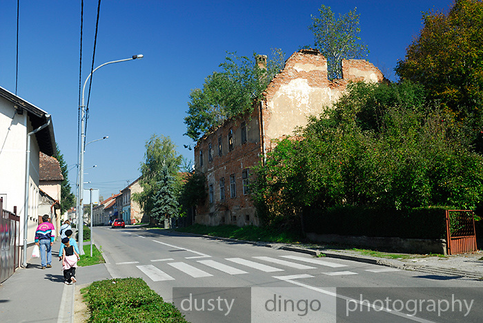 Street scene, with abaondoned war-damaged building. Petrinja, Croatia