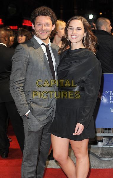 Richard Coyle & guest.'W.E.' UK film premiere, 55th BFI London Film Festival, Empire cinema, Leicester Square, London, England..23rd October 2011.LFF half length black dress grey gray suit.CAP/BEL.©Tom Belcher/Capital Pictures.
