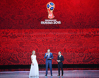 25.07.2015. St Petersburg, Russia.  Presenter Natalia Vodianova (L), FIFA Secretary General Jerome Valcke (C) and presenter Dmitry Shepelev stand on stage during the Preliminary Draw of the FIFA World Cup 2018 in St. Petersburg, Russia, 25 July 2015. St. Petersburg is one of the host cities of the FIFA World Cup 2018 in Russia which will take place from 14 June until 15 July 2018.
