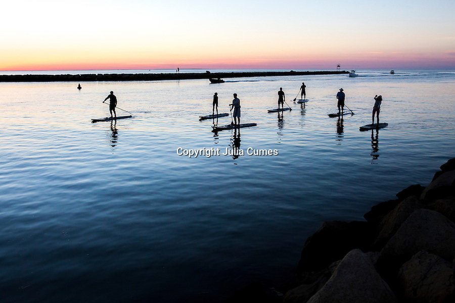 Stand up paddle boarders head out for a paddle at sunset on Cape Cod.