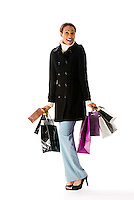 Young woman carrying shopping bags on white background