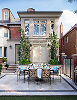 A table is laid for lunch and set on an outside terrace at the rear of this Georgian styled town house.