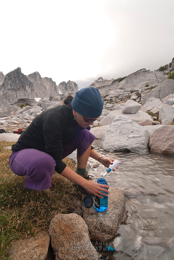 Female hiker using steri-pen water purifier in alpine tarn, top of  Asgard Pass, enroute to the Enchantments, Alpine Lakes Wilderness, WA.