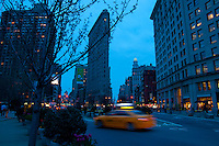 Yellow taxi passing by Madison Square, Broadway and Flatiron building in the evening