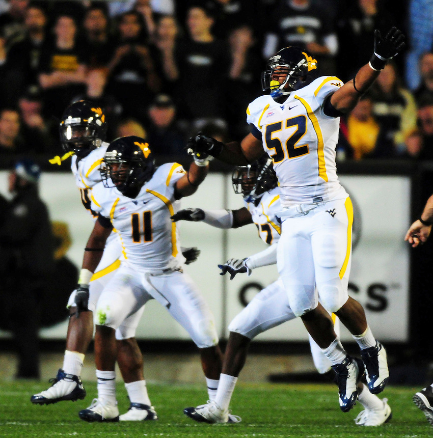 18 September 08: West Virginia defensemen, from left, Eain Smith, Sidney Glover, Brandon Hogan, and Najae Goode celebrate a fumble recovery in a game against Colorado. The Colorado Buffaloes defeated the West Virginia Mountaineers 17-14 in overtime at Folsom Field in Boulder, Colorado. For Editorial Use Only.