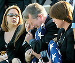 With his wife, Jeannine Wise head resting on his shoulder for comfort, David Wise (C), father of slain Florida National Guard Spc Robert Allen Wise clutches the Bronze Star and Purple Heart along with the American flag as he fights hard to control his emotions during his son's funeral at Arlington National Cemetery in Washington, DC November 24, 2003.  Wise's mother Tammy Wise  (R) sits transfixed in thought while the slain soldier's girlfriend Jenny Walsh (L) listens during the ceremony..