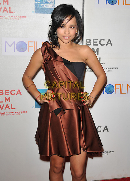 """ZOE KRAVITZ.9th Annual Tribeca Film Festival """"Beware The Gonzo"""" Premiere  held at Tribeca Performing Arts Center, New York, NY, USA..half length black brown silk satin one shoulder dress hands on hips pleats pleated .CAP/ADM/BM.©Bill Menzel/AdMedia/Capital Pictures."""