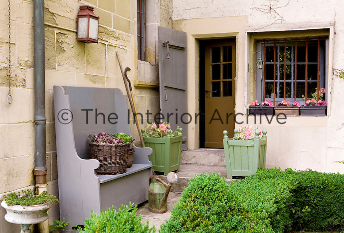 The mellow stone walls of the house are a perfect backdrop for the grey and green painted garden furniture