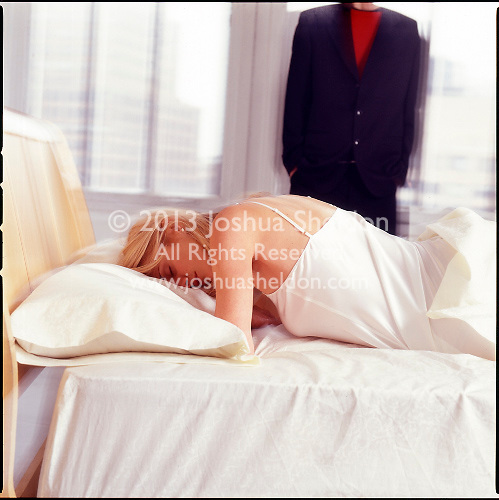 Woman in bed with man in background along window