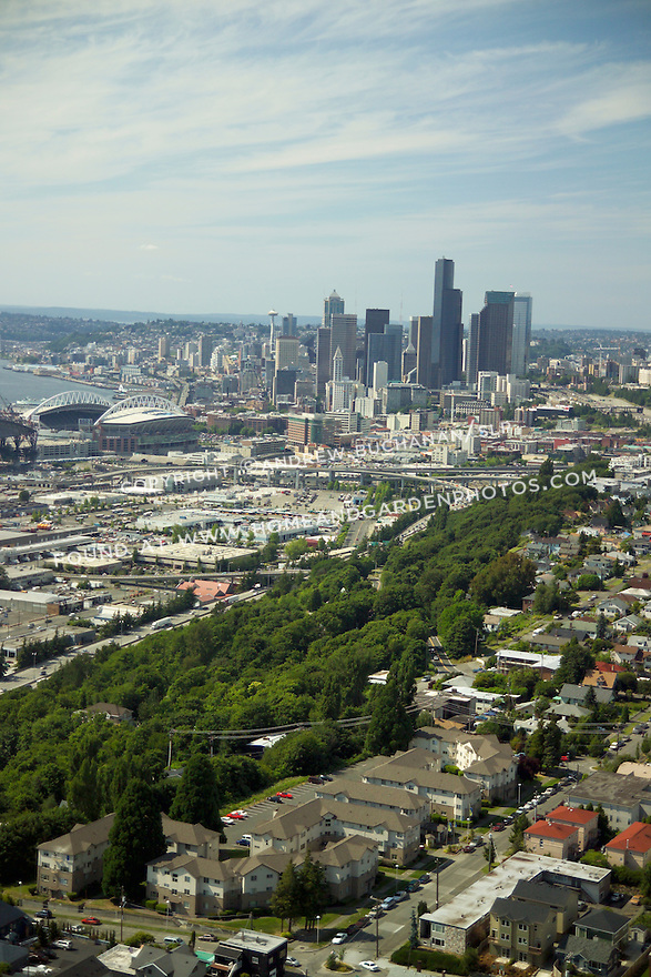 Sunny, summer, blue sky aerial view from above Seattle's Beacon Hill neighborhood, looking north to Qwest Field and the skyscrapers of the downtown Seattle skyline beyond.