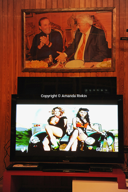 A Russian music video is seen on the television in Ibrahim Ibrahimov's living room underneath a picture of Ibrahimov (left) with Arif Pashayev, the father of the First Lady of Azerbaijan, Mehriban Aliyeva, Sangachal and Sahil, Azerbaijan on August 16, 2012.