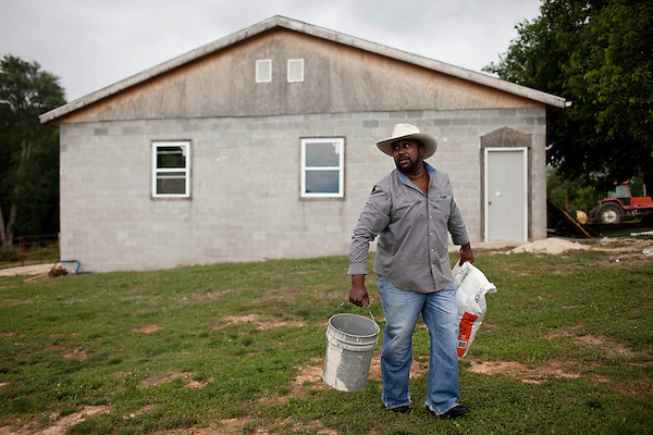 May 22, 2010. Baskerville, Virginia.. John Boyd, Jr. gets feed ready for the cattle on his farm that has been in the family for over 100 years.. Dr. John Boyd, Jr., a Virginia farmer, has lobbied the White House and Congress for the better part of two decades on behalf of black farmers. .A $1.25 billion settlement he helped to negotiate in February for the federal government to compensate black farmers has become ensnared in Washington. .Meanwhile, many elderly farmers who stand to benefit are dying before they can seek restitution..Their case, known as the black farmers settlement, and commonly referred to as Pigford II, is the second phase of a federal lawsuit settled in 1999. It covers more than 80,000 farmers who claim they were denied critical aid comparable to what white farmers received from the Department of Agriculture between 1981 and 1996 because of the color of their skin..Congress reopened the case in 2008, and set aside $100 million to address the late claims. President Barack Obama, who co-sponsored the 2008 measure when he was in the Senate, created a $1.15 billion line item in his budget for the 2010 fiscal year to cover the new class of litigants..The money was less than half of the $2.5 billion the farmers had fought for, but the administration's promise of a quick resolution prompted them to accept the deal.  .