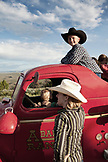 USA, Wyoming, Encampment, kids play in and on an old firetruck, Abara Ranch